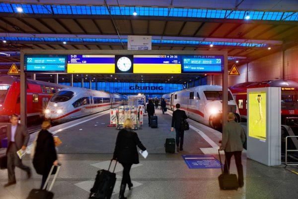 Reisende auf dem Weg zu Bahngleisen der deutschen Bahn ICE