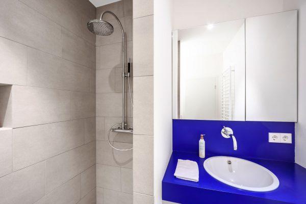 moderne dusche mit blauen waschbecken
