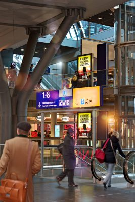 Bahnhofshalle Reisender geht an Stroer infoscreen vorbei