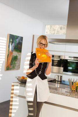 frau in küche mit kochbuch