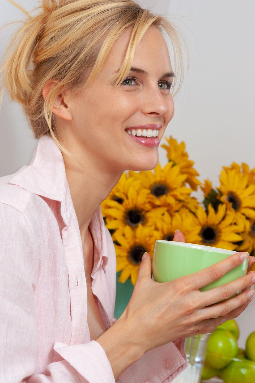 lachende frau mit tasse kaffe und sonnenblumen