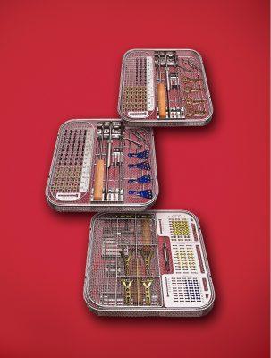 op-siebe mit implantaten und werkzeuge vor rot