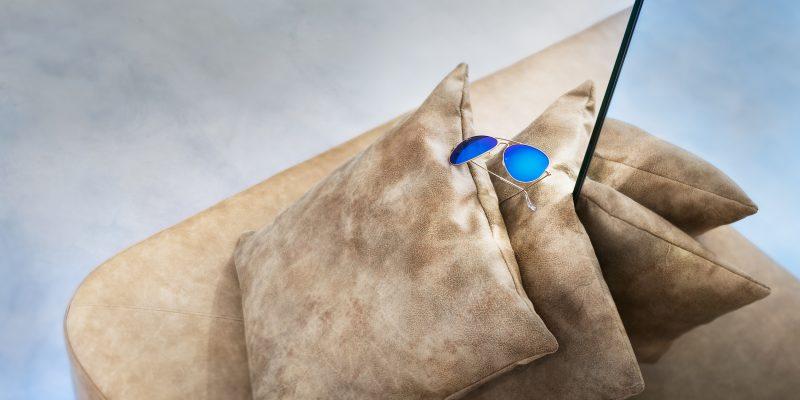 Blaue Sonnenbrille auf Lederpolster